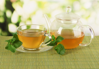 Cup of tea with mint on table on bright background