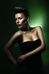 pretty beautiful woman with red lips in dark green light