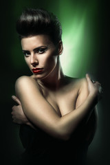 pretty woman with red lips in dark green light