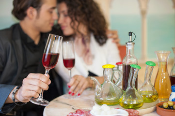 Young couple in restaurant, soft focus on glass