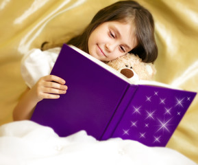 Adorable little girl reading book with her toy be