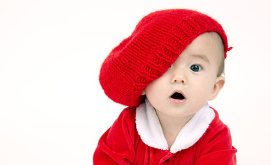 Infant Boy Sits lOOKING under his red hat