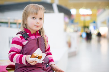 Adorable girl eat chocolate donut sitting on bench in huge store