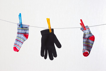 Baby socks and gloves are drying on a clothesline