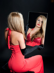 young woman in red dress looks into a  mirror on dark background