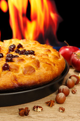 tasty homemade pie with jam, on wooden table on flame
