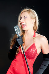 Portrait of a blonde woman in red dress with a retro microphone