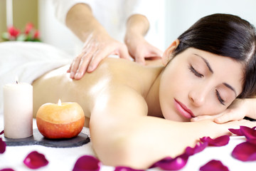Happy relaxed woman getting back massage in luxury spa