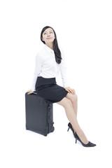 スーツケースに座る女性