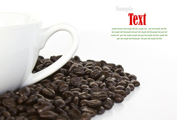 Close up of coffee beans and coffee cup on white background with