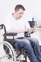 Man in wheelchair with tablet computer at work