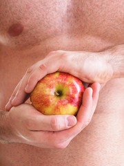 Muscle naked young man torso red apple in hands