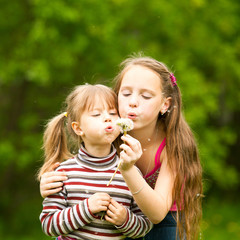 Cute 5 year old and 11 year old girls blowing dandelion.