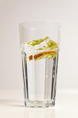 Kiwi slice dropped into glass of refreshing water