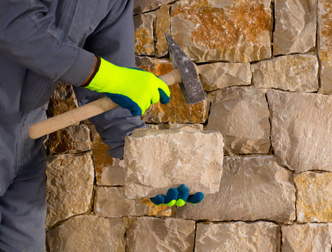 stonecutter mason with hammer and stone working masonry