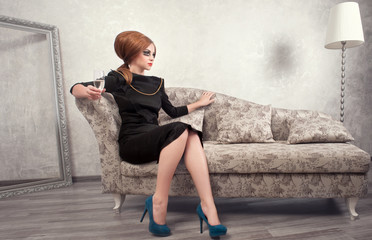 The image of a beautiful woman sitting on a gold vintage couch