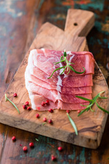 Prosciutto Crudo with rosemary on wooden chopping board