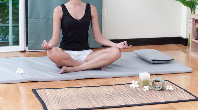 A woman doing yoga exercise on yoga mat at home