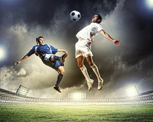 Photo sur Aluminium Le football two football players striking the ball