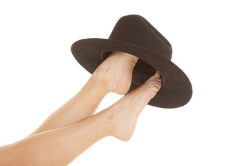 Woman feet cowboy hat on both