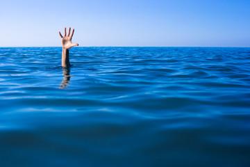 Help needed. Drowning man's hand in sea or ocean. Fototapete