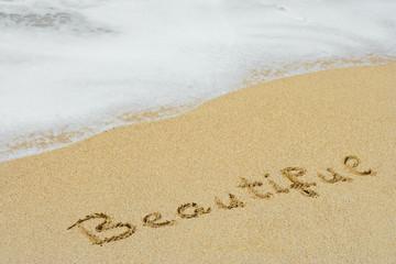 Conceptual handwritten text beautifue in sand