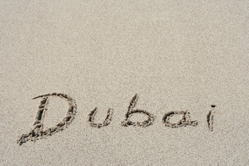 Conceptual handwritten text Dubai in sand