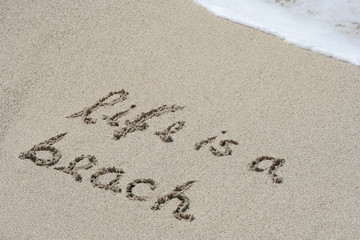 Conceptual handwritten text life is a beach in sand