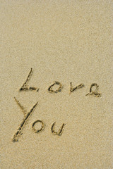 Conceptual handwritten love you text in sand