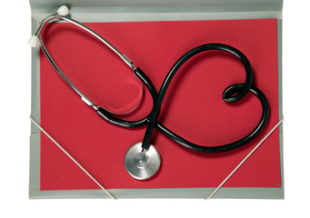 Stethoscope with heart shape is lying on paper