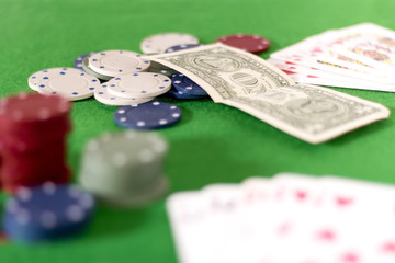 Poker game, chips and cards on green baize