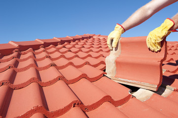 Construction worker tile roofing repair house