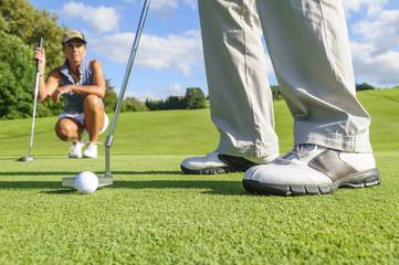 Golferin beobachtet den Putt