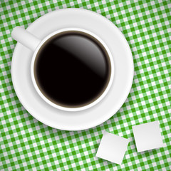 Cup of coffee on green tablecloth