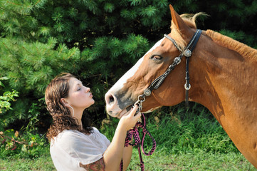 Young adult woman kissing her horse