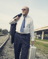 Angry, jobless senior businessman walking along railroad tracks