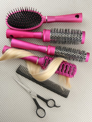Comb brushes, hair and cutting shears, on grey background