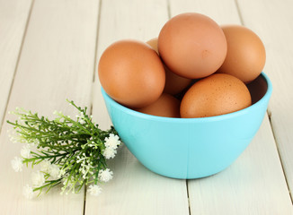 Eggs in blue bowl on wooden table close-up