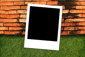 Photo frame on green grass and brick wall