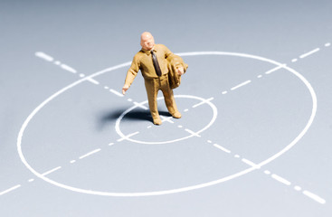 miniature figure of businessman standing on a sight symbol