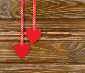 Two red hearts on a brown background