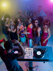 dj mixing music at party with dancing people