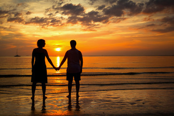 Romantic picture: Silhouettes young couple on the beach.