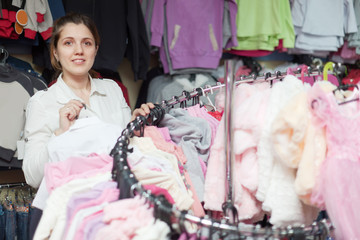 woman chooses white blouse at  shop