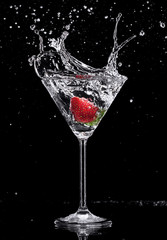 Deurstickers Opspattend water Martini drink splashing out of glass on black background