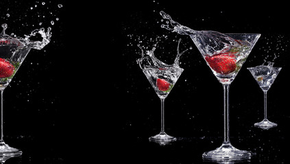 Martini drinks with splashes, isolated on black background