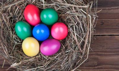 Farbige Ostereier im Nest auf Holz VI