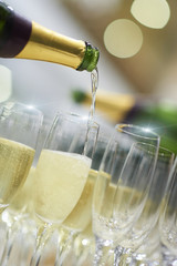 Champagne bottles pouring into glasses