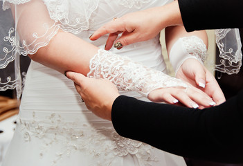 Young bride dresses gloves
