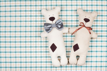 Handmade toy bears pair on checkered textile background